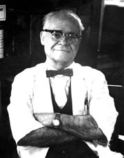 Picture from the waist up of a white man, perhaps in his 60s, with his arms crossed in front of him. He is wearing eyeglasses, a white shirt with bow tie, and a dark apron.