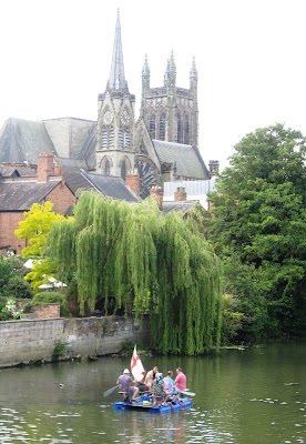 Raft on river with weeping willow and church tower in the background