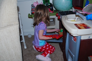 Preschooler putting cookies in the oven for her little dolls
