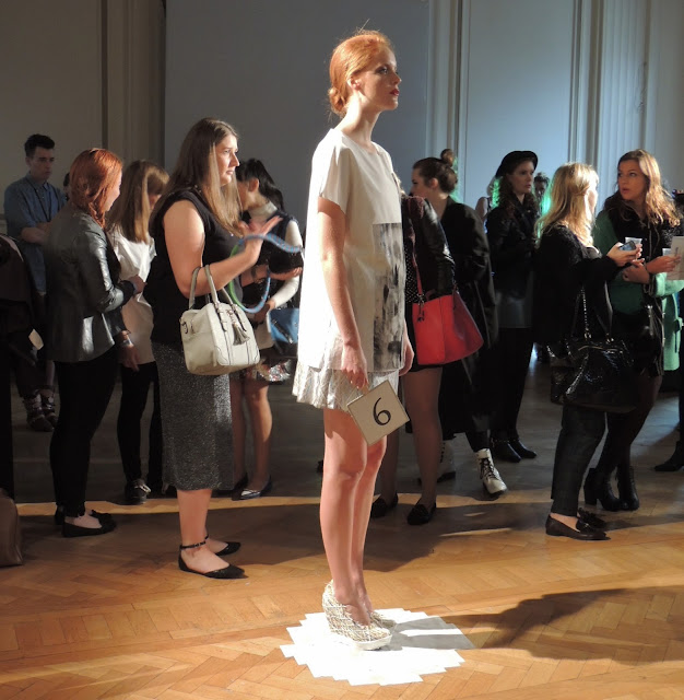 Model in white stands in front of London Fashion Week bloggers