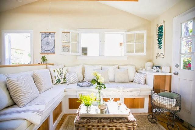 Living room in a small cottage with a built in sofa, sea grass rug and rattan coffee table
