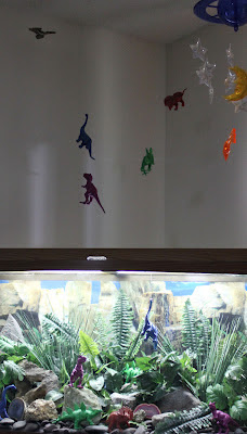 dinosaurs levitating over a Jurassic fish tank starship enterprising near ceiling