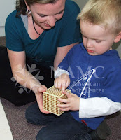 NAMC montessori teacher and child play with thousand block why we believe in the montessori method