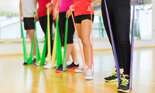People doing exercises with resistance bands for the lower body.