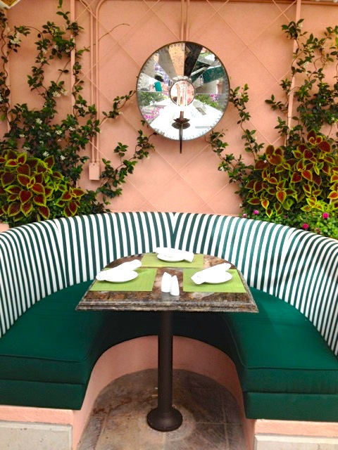 Outdoor green and white striped booth poolside restaurant