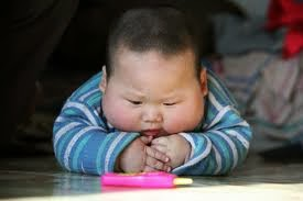 bebe asiatico mira un caramelo