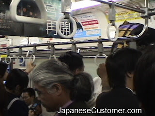 Japanese customers commuting in Tokyo copyright peter hanami 2005