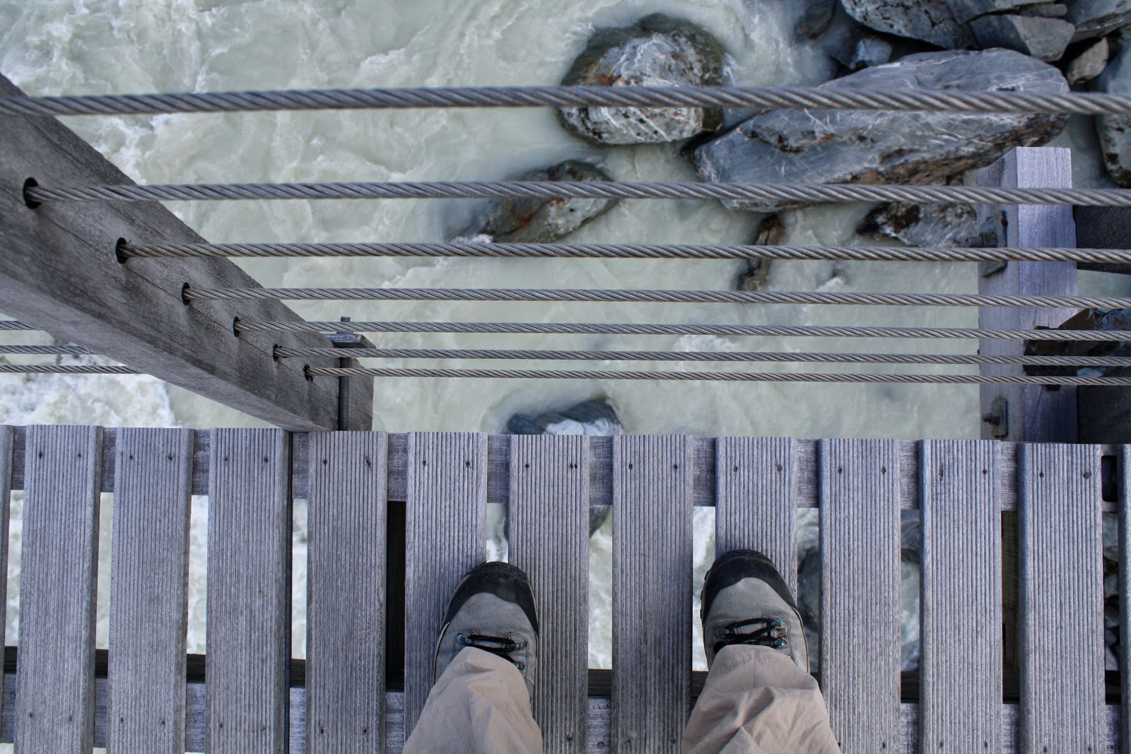 Looking down at my feet on a suspension bridge, the river far below.