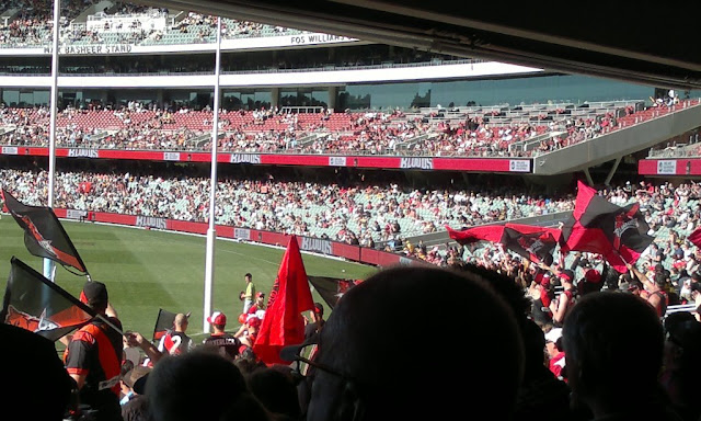 View from the bottom tier of the Adelaide Oval southern stand. One can see the four tiers of the eastern stand and the crowds.  Behind the goals the crowd is a sea of red and black guernseys and flags and banners.