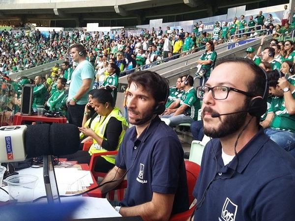 Em primeiro plano os audiodescritores Dimitri à esquerda e Bruno à direita sentados em uma mesa usando fones de ouvido e com microfones, ao fundo os deficientes visuais sentados ao lado de seus acompanhantes
