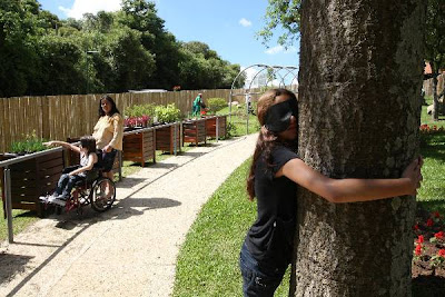 treino sensorial: a imagem mostra uma rapariga vendada, que abraça uma árvore.