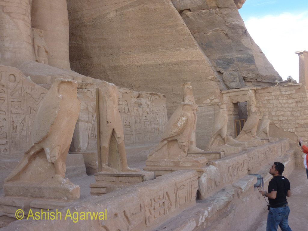 Tourist admiring some of the statues at the foot of the Abu Simbel temple in Egypt