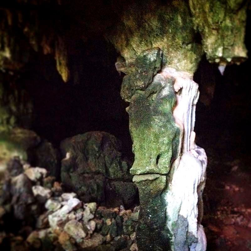 """Antes de entrar, nuestra guía nos pide que no toquemos nada y respetemos el lugar. Insiste en que no tomemos ninguna piedra por pequeña que sea, """"no debemos enfadar a los guardianes"""". Perder al respeto a los lugares sagrados puede ser peligroso.  Antes de entrar a la caverna, siguiendo el rito maya, Lourdes pide permiso a los guardianes para realizar nuestra visita. Nos dice que los antiguos mayas dejaron poderosos espíritus invisibles para que protegieran estos lugares.  En la entrada hay enorme roca de color verde. Completa parece una boca de ave o serpiente, y en su mitad superior se ve un ser con cabeza cuadrada y alargada. Su dentadura parece la de un esqueleto."""
