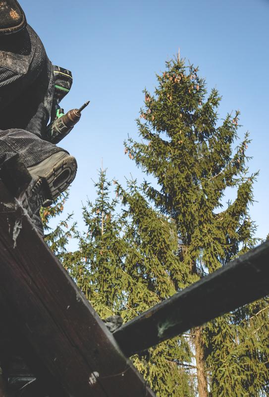 Bauarbeiterhintern zwischen freigelegten Dachbalken und blauem Himmel