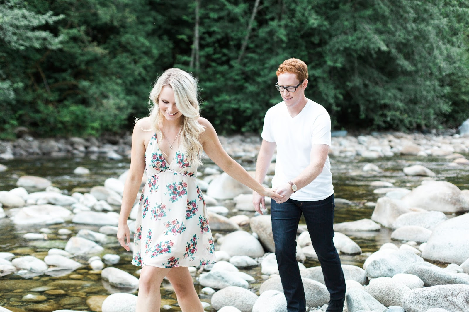 a blonde women and red haired man walk along riverside, happy and newly engaged in love