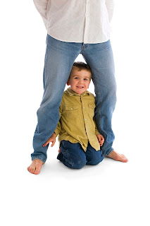 Photo of a happy child peering out from behind his father's legs.