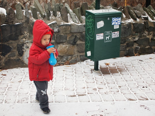 boy spraying food coloring onto snow to paint it