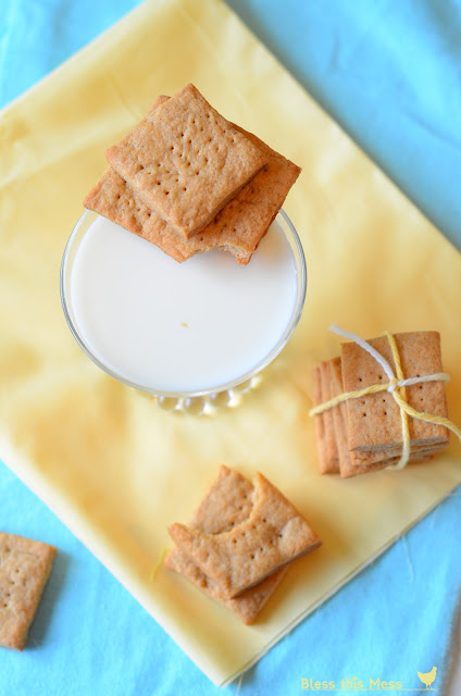 Graham Crackers sitting next to a glass of milk on a yellow cloth