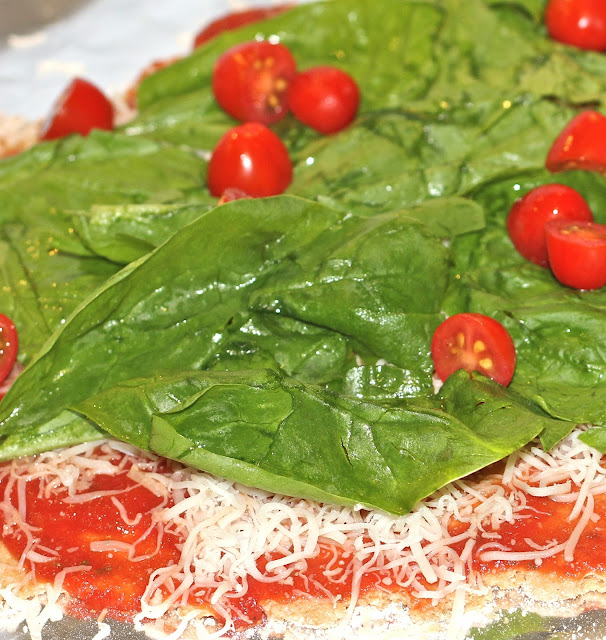 Spinach and baby tomatoes atop a wholewheat pizza on www.anyonita-nibbles.com