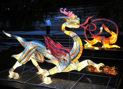 Visitors walk beside colorful lanterns ahead of the Seoul Lantern Festival at the Cheonggye stream in central Seoul on October 31, 2013. The festival is part of a campaign by South Korea to attract more foreign tourists and runs from November 1 to 17