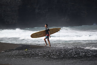 Surfer at Waipi'o Valley's black sand beach