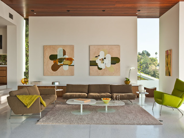 Picture of the sitting room with brown sofa and green chairs along with the paintings on the white wall