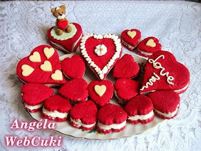 Valentin napi kicsi és nagy szív alakú, piros kekszek, tejszínes fehér csokoládés krémmel töltve.