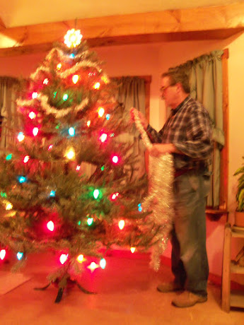 Jim decorating with garland the big tree in our great room