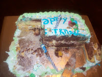 A largely eaten birthday cake with cutting knife in view