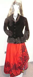 maniquí vestido con traje tradicional: falda roja, chambra negra y mantilla