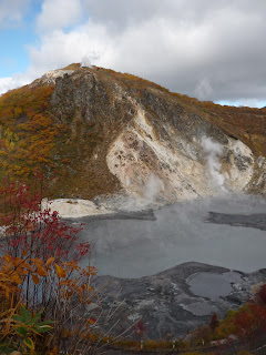 Sulfurous lake near noboribetsu-onsen's Jigokudani (Hell valley) with steam, mud, a hill will autumn (fall) coloured leaves on the trees