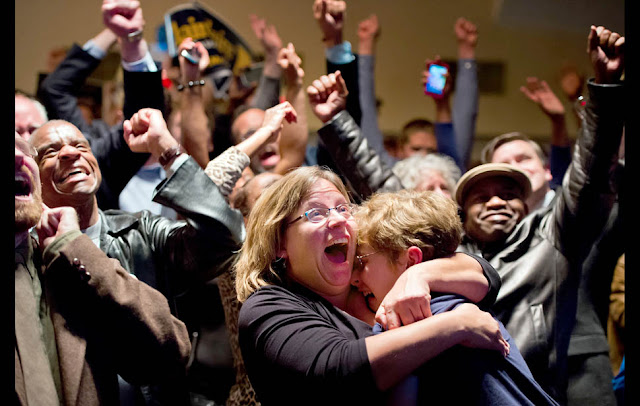 St. Louis — Michelle Zielinski, center, hugs Jared Goudsmit after President Barack Obama is projected to win during an election watch party at the Chase Park Plaza Hotel.