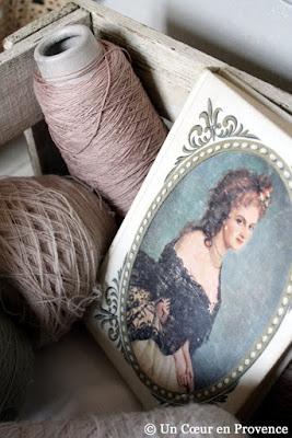 Mise en scène romantique avec un vieux casier à bouteilles en bois, d'anciennes bobines de fil et des pelotes de laine