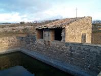 Vista de la bassa de Cal Magí de les Alzines amb el mecanisme exterior de la sínia per extreure l'aigua
