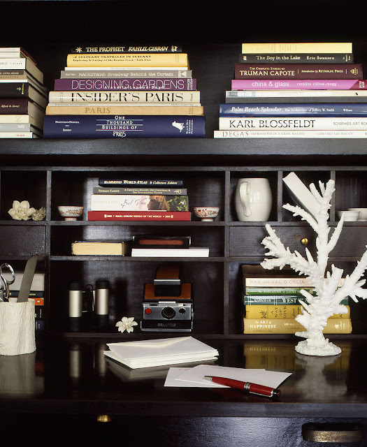 close up of anthony cochran's built in book shelf cabinet painted black with gloss paint holding books and small trinkets