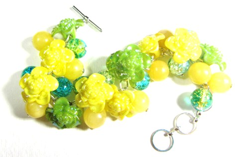 Bracelet has yellow flower buttons, crackle beads and Aragonite