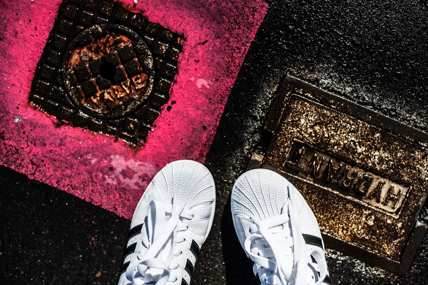 Adidas Superstar black and white sneakers looking straight down with coloured pavement