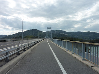 View along road deck of the Hakata Oshima bridge, first part is the girder bridge, with the suspension bridge section visible in the distance. Mountains of Oshima are visible in the backgound. On the Shimanami Kaido Bikeway