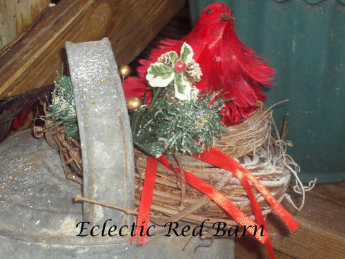 Red Bird Perched on a Nest on the Opening of the Watering Can