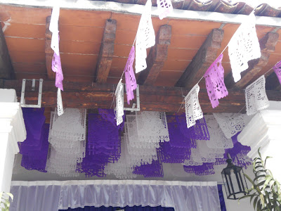 Purple and white papel picado banners over the offering