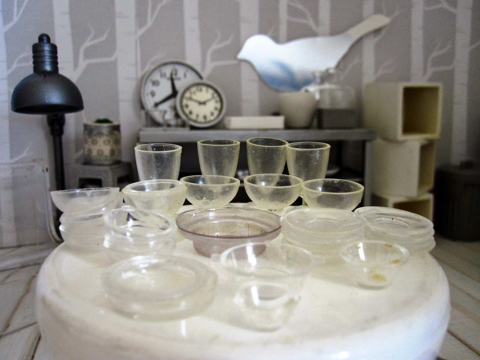 Close up of  a modern dolls' house miniature display of glass bowls, plates and glasses, set out on a round white table in a homeware store.