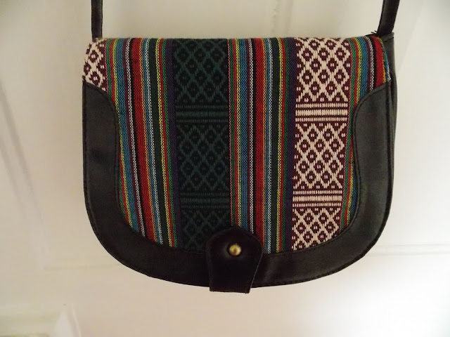 Close up of black cross-body bag with Aztec/tribal design