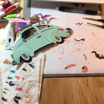 Work table with paints, paintbrushes, pencil and cut paper along with light green Volkswagen Beetle made out of paper