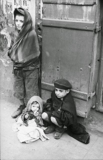 Três crianças judias, famintas e com frio no gueto de Varsóvia, durante a Segunda Guerra Mundial.