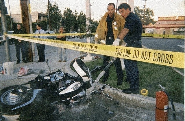 Motorcycle accident investigation scene that occurred at an intersection and severed a man's foot. Image shows a motorcycle on road with area taped off for investigation and police officers and investigators reviewing accident scene. City buildings in background.