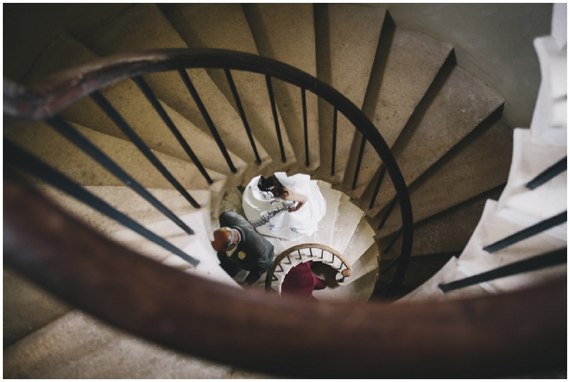 Bride walking up spiral staircase in castle