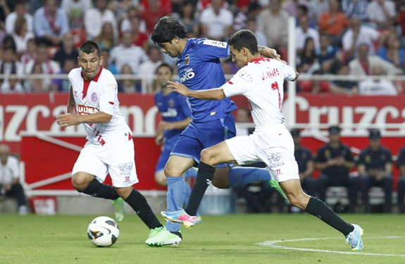 Éver Banega skips past Sevilla players before scoring the opening goal for Valencia