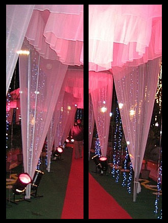 Pink sheer fabric is gathered in tented columns and illuminated with spot