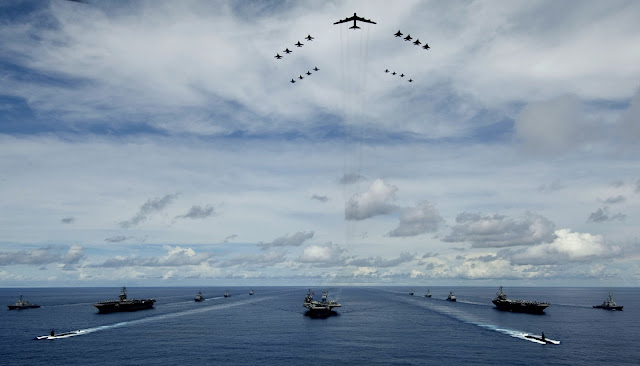 A B-52 Stratofortress leads a formation of Air Force and Navy F-16 Fighting Falcons, F-15 Eagles, and F-18 Hornetst over the USS Kitty Hawk, USS Nimitz and USS John C. Stennis Strike Groups during Exercise Valiant Shield.