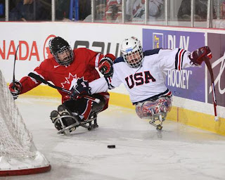 USA sled hockey team player and a Canadian sled hockey player both go after the puck on the ice rink.